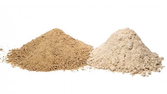 2 piles of rice bran next to each other on a white background. Pile on left is a dark brown and pile on right is a light tan.